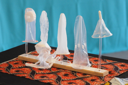 different types of condoms are displayed on sticks on a table