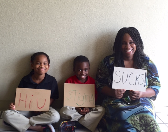 "Morénike Giwa Onaiwu sits with two of her children holding signs that read ""HIV Stigma Sucks"""