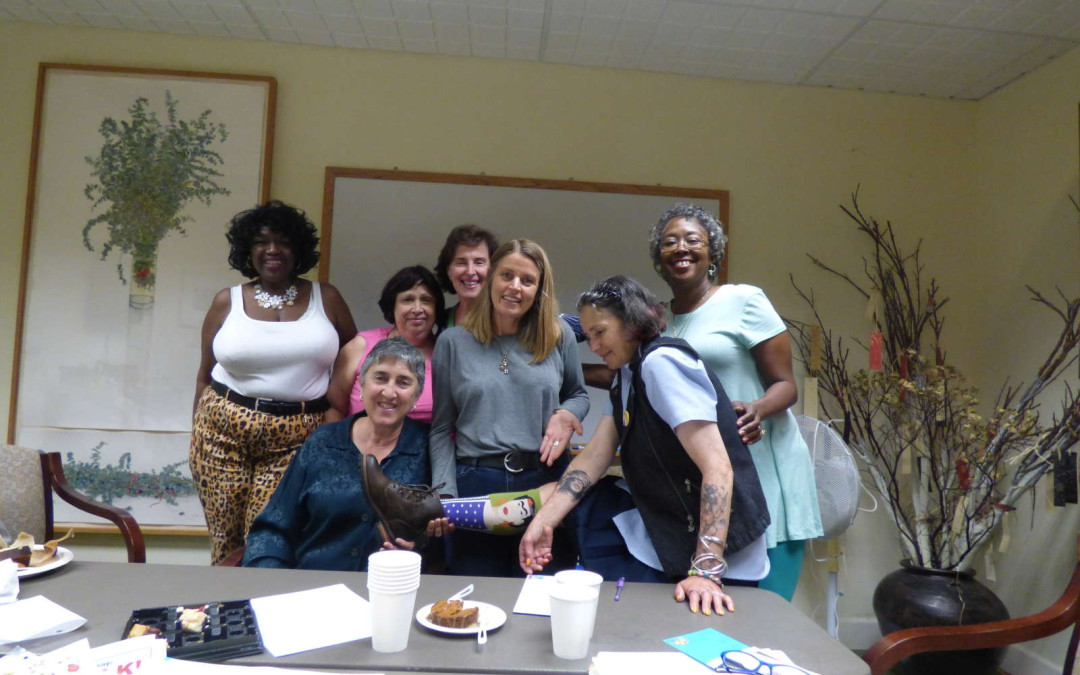 a multi-racial group of older women smile and hug behind a table