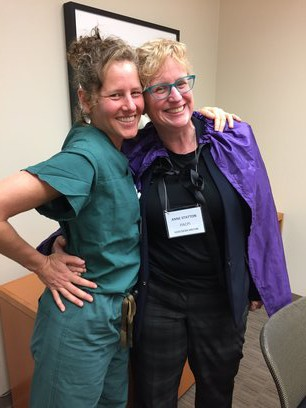Dr. Deb Cohan hugs Anne Statton who is wearing a cape