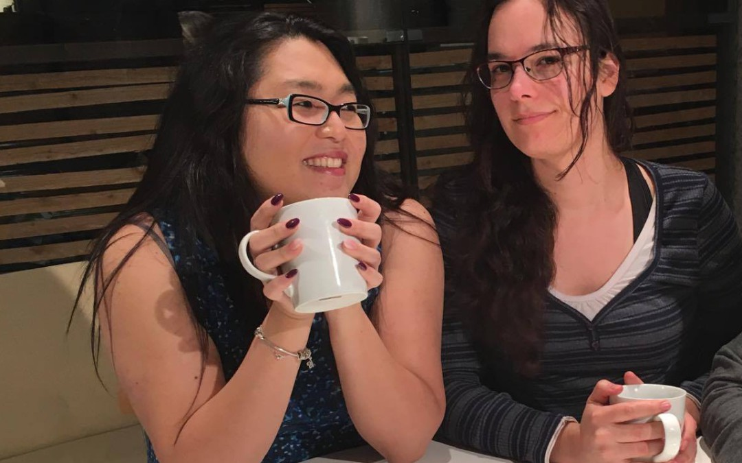 an Asian woman and a white woman sit drinking coffee