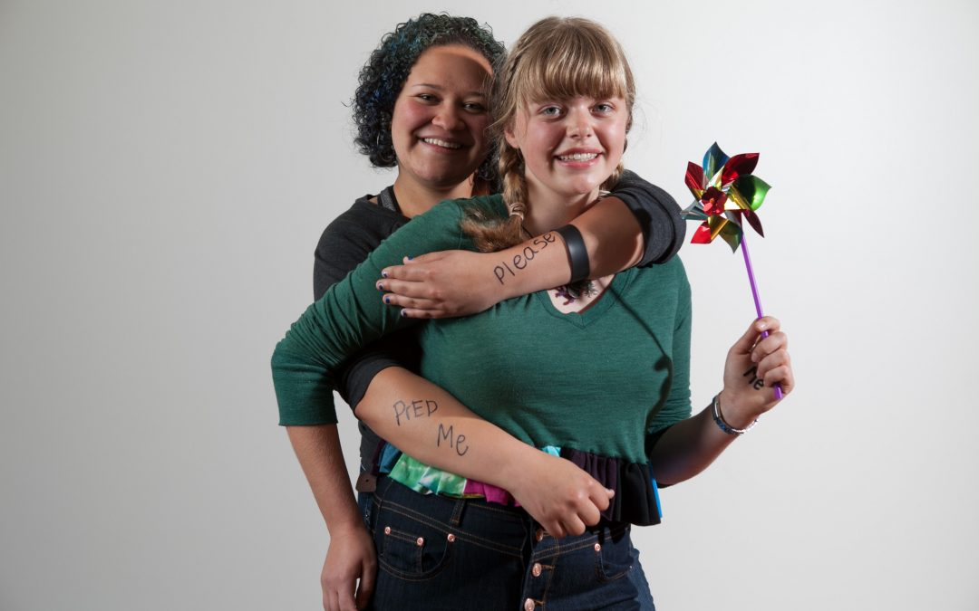 a Black teen girl hugs a white teen girl, they have PlesePrEPMe written on their arms