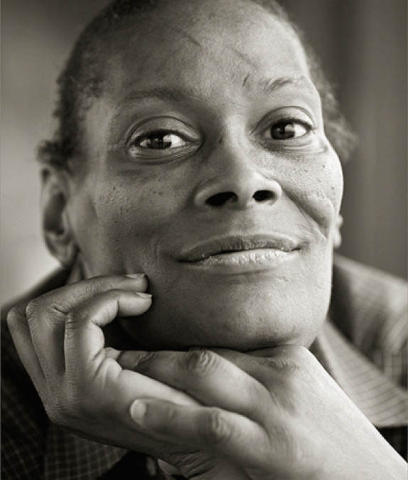 black and white image of older Black woman smiling at camera