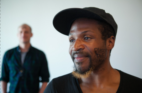 Black man with PleasePrEPMe written on his cheek looks to the side, blurry white man stands behind him