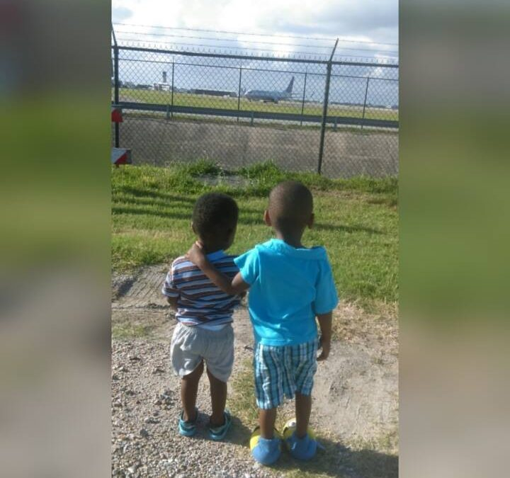 two little Black boys look at airplanes