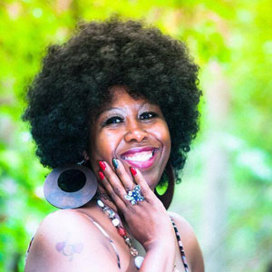 Black woman with afro and jewelry smiles at camera