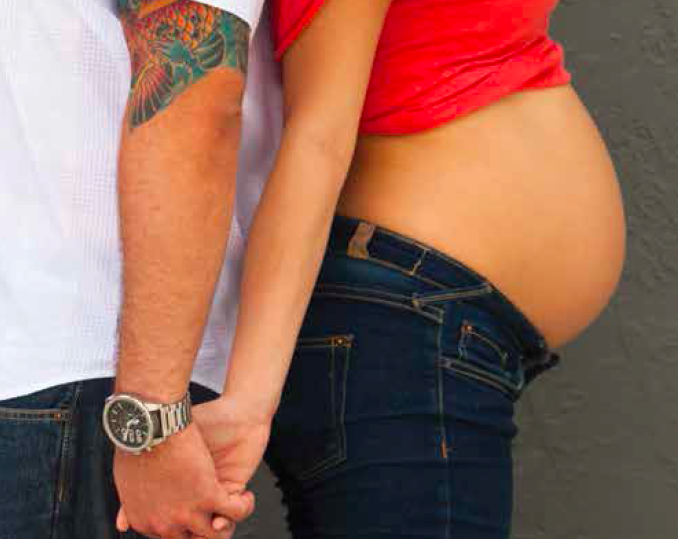 midsections of white couple, woman is pregnant