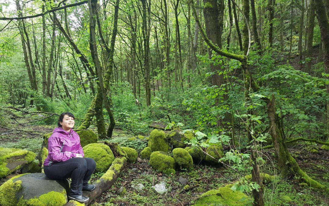 Maureen sits in a green forest