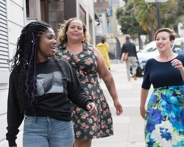 Three women, white, Black, and mixed, walk down the street